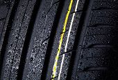 picture of asymmetric  - wet tire with asymmetric tread detail close - JPG
