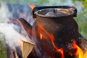 picture of bonfire  - Bonfire with metal old black boiling teapot on it  - JPG