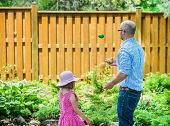 picture of juggling  - A little girl watches her father juggling colorful Easter eggs outside in a beautiful garden during the spring season - JPG