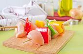 stock photo of raw chicken sausage  - raw kebab on board and on a table - JPG