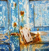 stock photo of nail paint  - stripped paint in the blue wood door and rusty nail - JPG