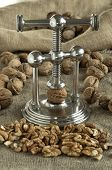 stock photo of nutcracker  - nutcracker and pile of walnuts in shell in soft diffused light - JPG