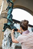 foto of perseus  - Young woman taking photo of statue perseus with the head of medusa in florence italy - JPG