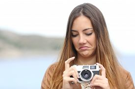 stock photo of disgusting  - Upset photographer woman looking her old slr photo camera disgusted with the sea in the background - JPG