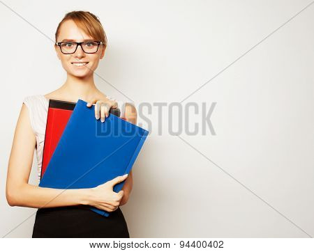 Beautiful young businesswoman holding folders while standing against grey background
