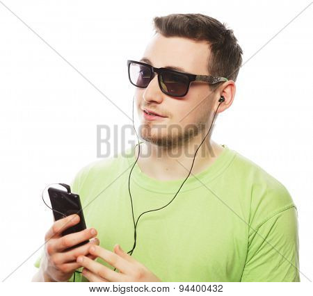 technology and people concept - young man wearing green t-shirt  listening music and using smartphone, isolated on white