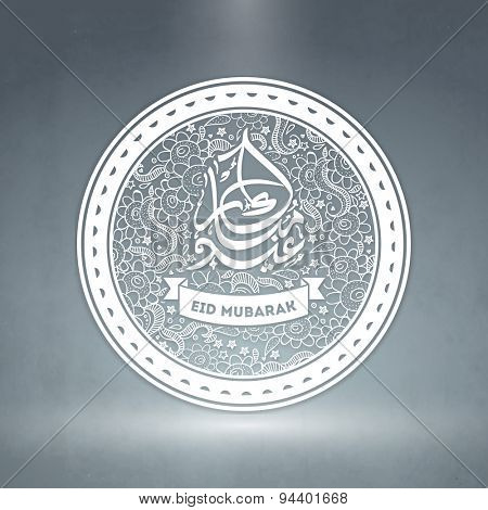 Beautiful sticky design decorated with artistic floral pattern and Arabic Islamic calligraphy of text Eid Mubarak on shiny background for Muslim community festival celebration.