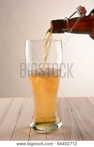 A brown swing top bottle of beer pouring into a glass. The partially filled glass is on a wood table with a light to dark background.