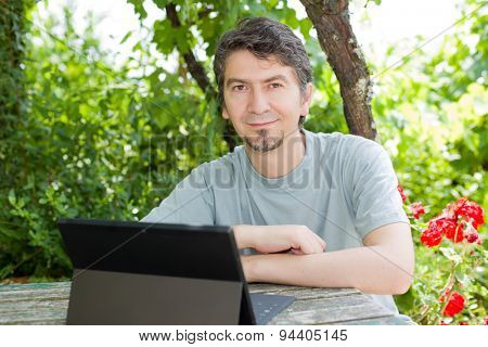 young happy man with a tablet pc, outdoor