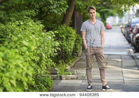 Young man standing on the summer street portrait in full growth.