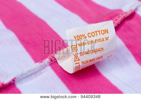 Label 100% cotton on a pink and white t-shirt