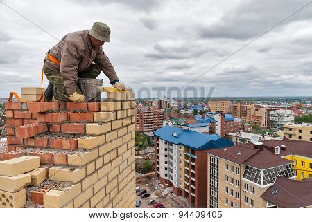 Bricklayer works on high house construction
