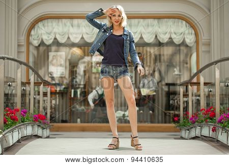 Portrait in full growth the young blonde woman in a blue jacket and jeans short against the backdrop showcase store