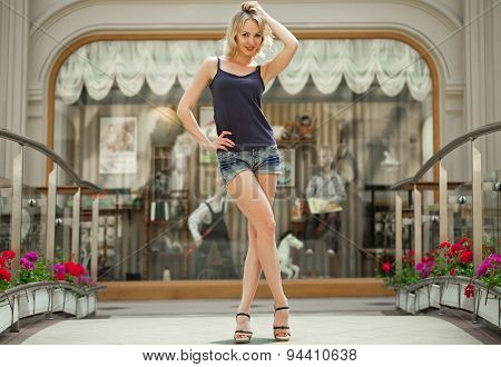Portrait in full growth the young blonde woman in a blue jeans short against the backdrop showcase store