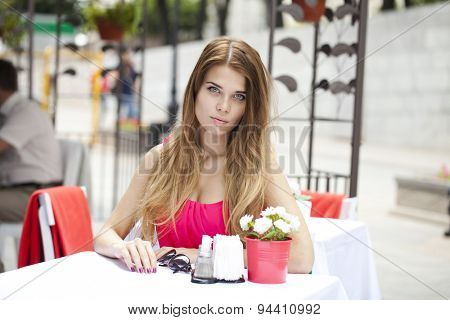 Young beautiful blonde girl sitting in a summer restaurant
