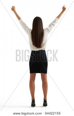 back view of happy businesswoman in formal wear raising her hands up. isolated on white background