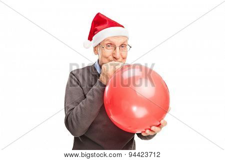 Cheerful senior with Santa hat blowing up a red balloon and looking at the camera isolated on white background