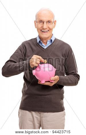 Vertical studio shot of a joyful senior putting a coin into a pink piggybank and looking at the camera isolated on white background