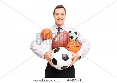 Young man holding a bunch of different kind of sports balls and looking at the camera isolated on white background