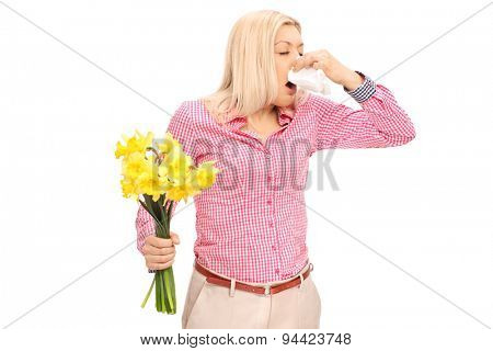 Young blond woman having an allergic reaction to flowers and blowing her nose isolated on white background