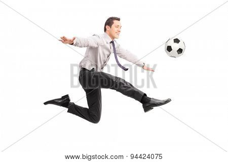 Studio shot of a young businessman kicking a football and smiling isolated on white background