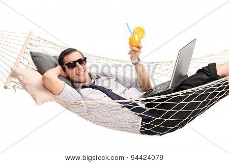 Young businessman lying in a hammock with a laptop in his lap and drinking an orange cocktail isolated on white background