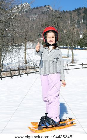 Young Girl With Orange Snowshoes And Helmet