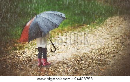 Happy Baby Girl With  Umbrella In The Rain Runs Through