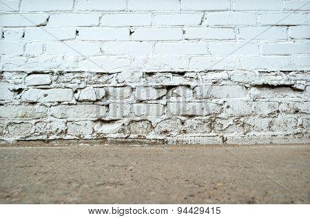 Empty grunge brick wall with ground floor