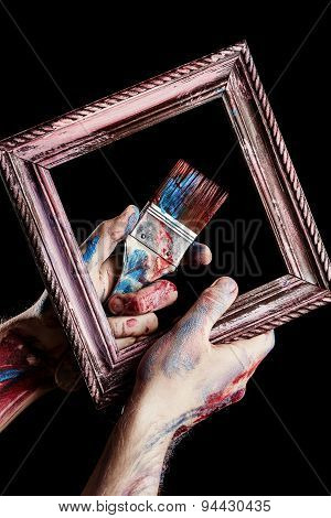 Paintbrush And Vintage Frame In Hands