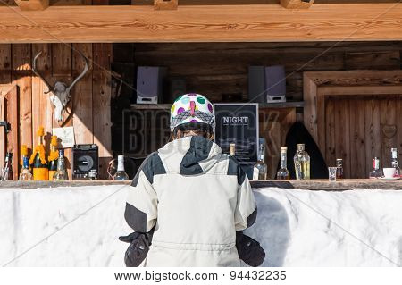 Rear View Of Woman Skiers Waiting At Mountain Lodge Counter For A Drink