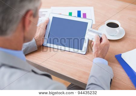 businessman holding tablet and credit card in his office