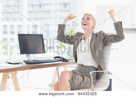 Businesswoman celebrating a great success in her office