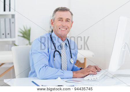 Concentrating doctor using computer in medical office