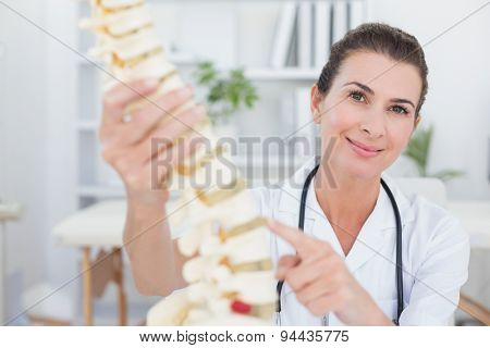 Happy doctor showing anatomical spine in medical office