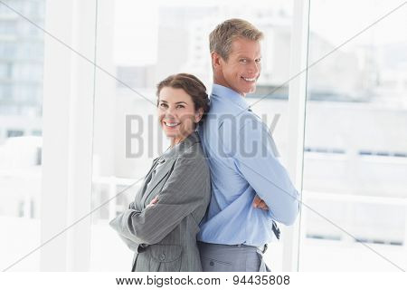 Smiling businesswoman back-to-back with colleague in an office