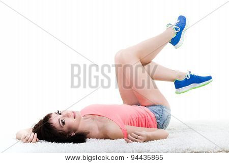 Sexy fitness young woman lying against isolated white