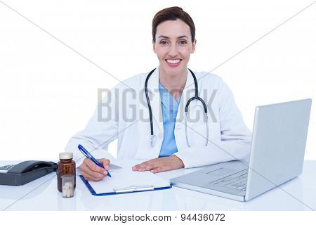 Smiling doctor writing on a notebook