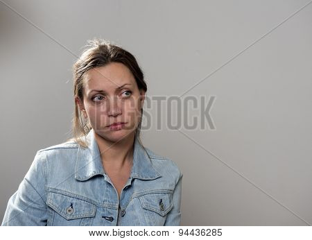 Portret of sad young woman in a denim jacket