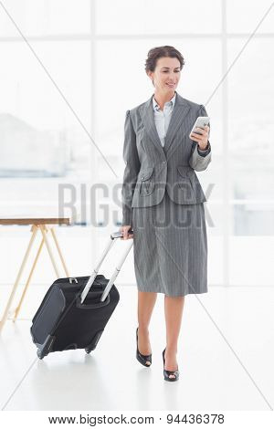 Full length of a beautiful young businesswoman text messaging while on a business trip