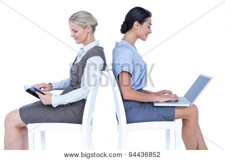 Businesswomen using laptop and reading book on white background