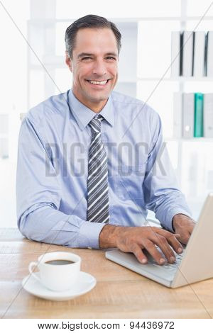 Smiling businessman using his computer in his office