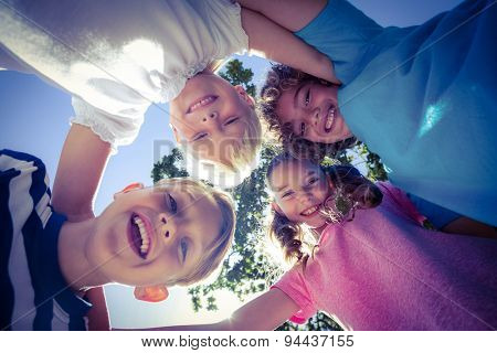 Smiling children forming a huddle in circle in the park