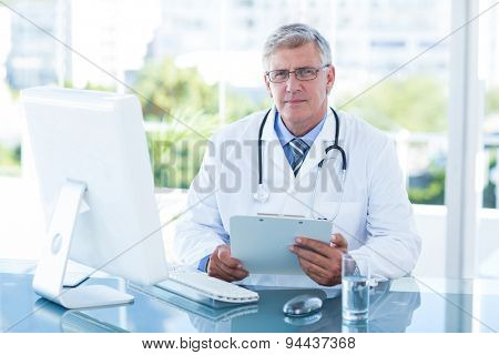 Smiling doctor working on computer at his desk in medical office