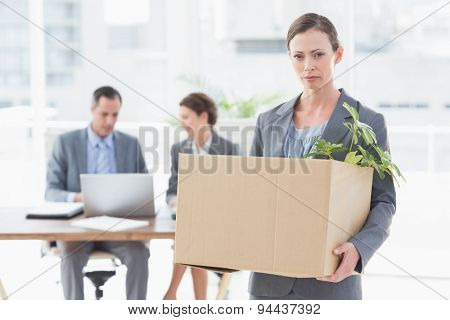 Businesswoman leaving office after being fired and carrying her belongings