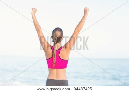 Wear view of fit woman looking at the sea with arms rise at the beach