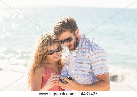happy couple looking at their camera on the beach