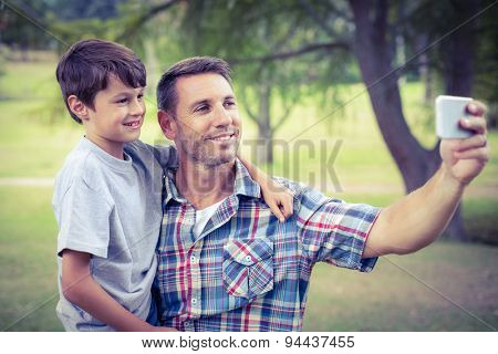 Father and son taking a selfie in the park on a sunny day