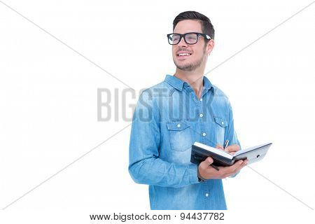 Geeky hipster taking notes in book on white background