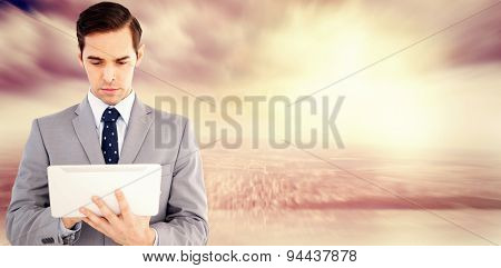 Businessman holding a tablet computer against room with large window looking on city
